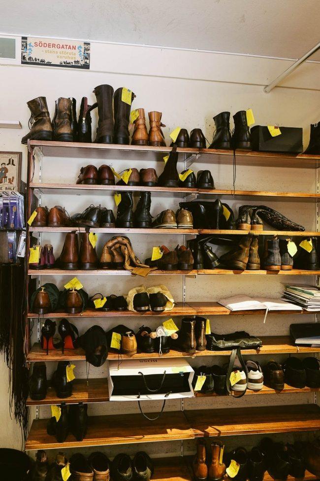 Prateleira na sapataria com sapatos para conserto