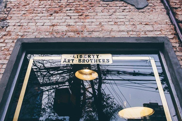 Lettering à mão na vitrine da Liberty Art Brothers