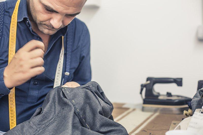 Alfaiate costurando uma calça à mão